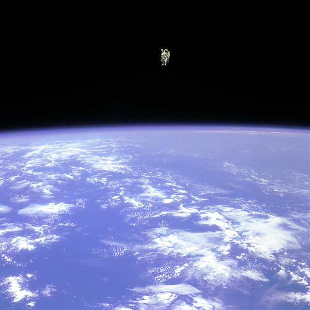 NASA photo of Earth from space with tiny astronaut floating alone in space